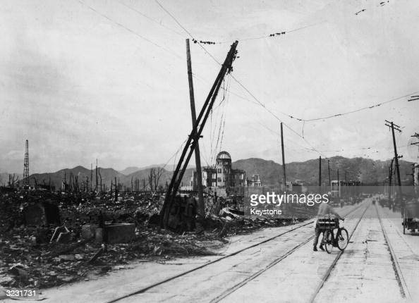 A man wheels his bicycle thorough Hiroshima days after the city was leveled by an atomic bomb blast Japan The view here is looking westnorthwest...
