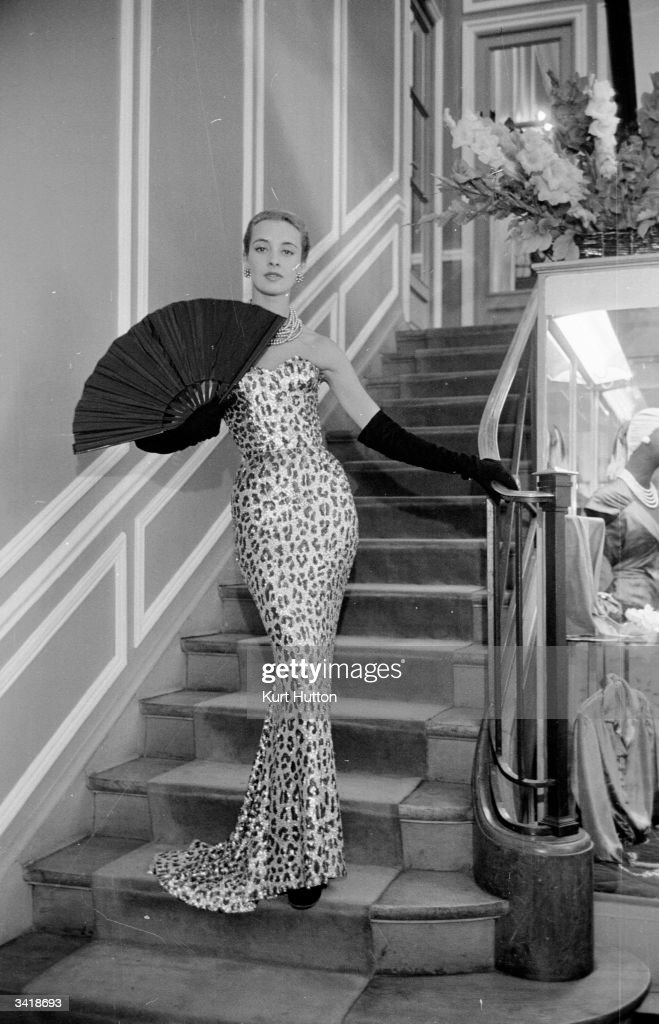 A model wearing one of Christian Dior's evening dresses from his Autumn / Winter collection in Paris. Original Publication: Picture Post - 6685 - Paris Picks Up Her Skirts - pub. 1953