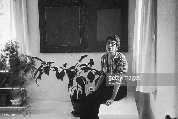 Abstract Expressionist artist Lee Krasner the wife of artist Jackson Pollock seated on a ledge at her home in East Hampton New York
