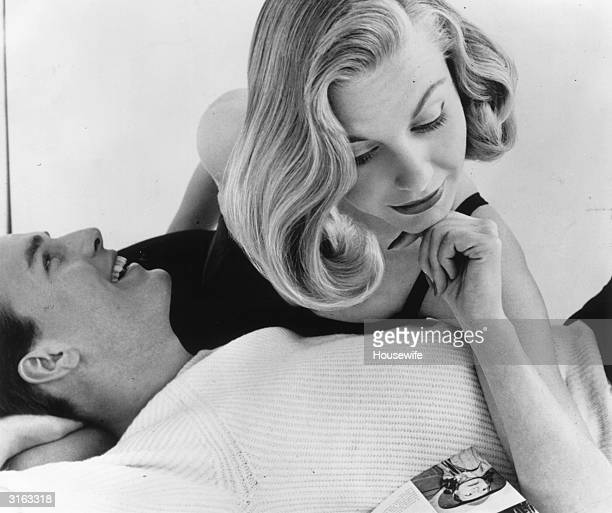 British model Shirley Worthington leans over a gentleman friend in order to read a magazine