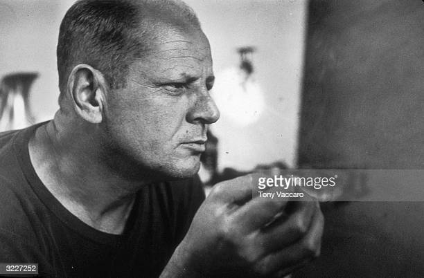 Profile headshot portrait of American Abstract Expressionist painter Jackson Pollock in his studio New York City
