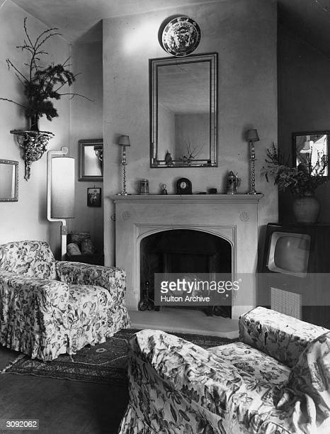 Interior of a fifties sitting room with the furniture arranged around the TV and fireplace
