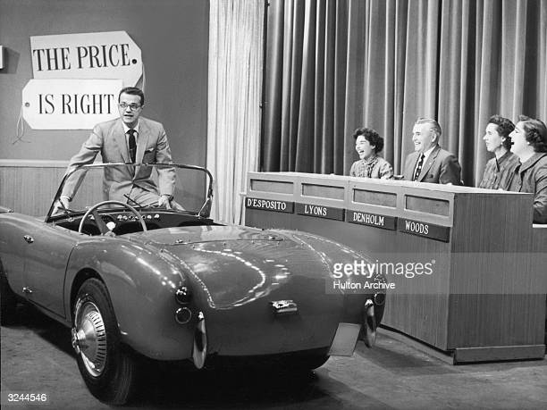 American TV host Bill Cullen sits on the edge of a convertible car as four contestants laugh in a still from the television game show 'The Price Is...