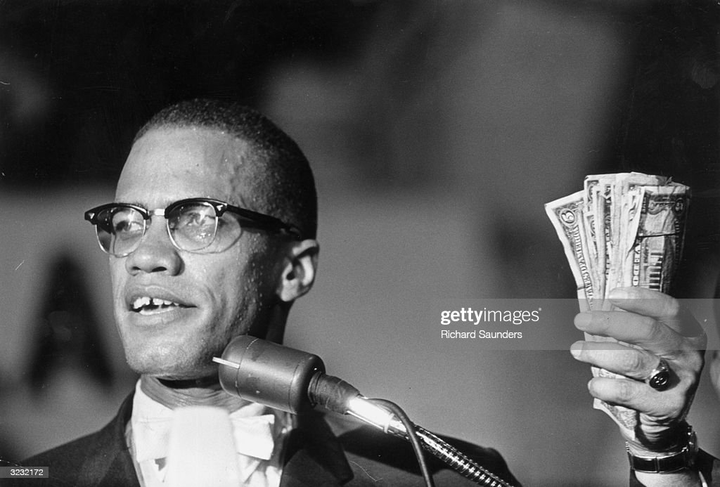 Headshot of American political activist <a gi-track='captionPersonalityLinkClicked' href=/galleries/search?phrase=Malcolm+X&family=editorial&specificpeople=70045 ng-click='$event.stopPropagation()'>Malcolm X</a> (1925 - 1965) holding a fist full of US currency during a speech at Urline Arena, Washington, DC.