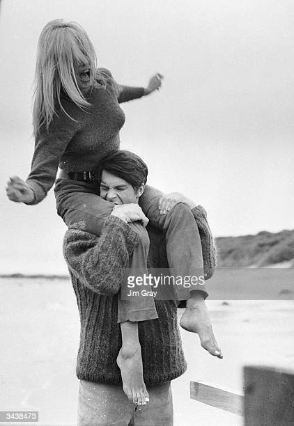 French actor Laurent Terzieff bites Brigitte Bardot's leg while giving her a piggyback ride on the beach at North Berwick Scotland in a scene from...