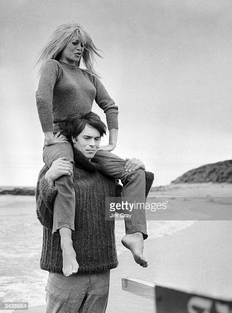 French actor Laurent Terzieff giving Brigitte Bardot a piggyback ride on the beach at North Berwick Scotland in a scene from the film 'Two Weeks in...