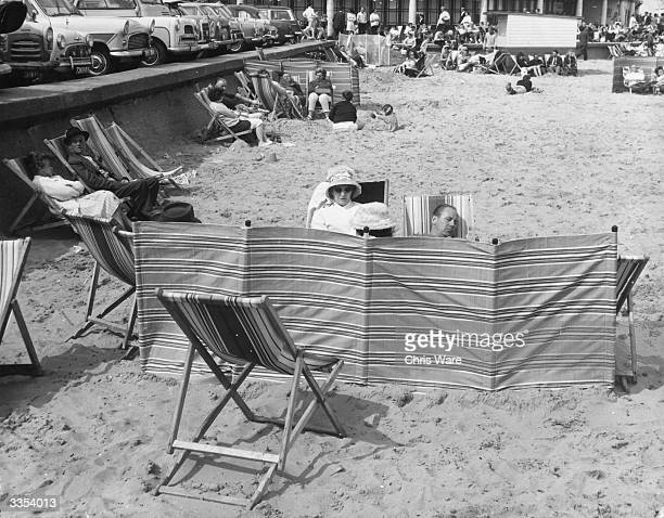 Holiday makers dozing behind a wind break on the beach at Great Yarmouth in Norfolk