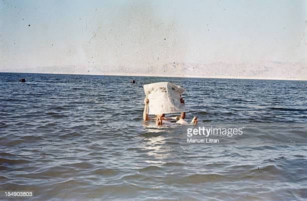 a bather reading the newspaper floating on the Dead Sea