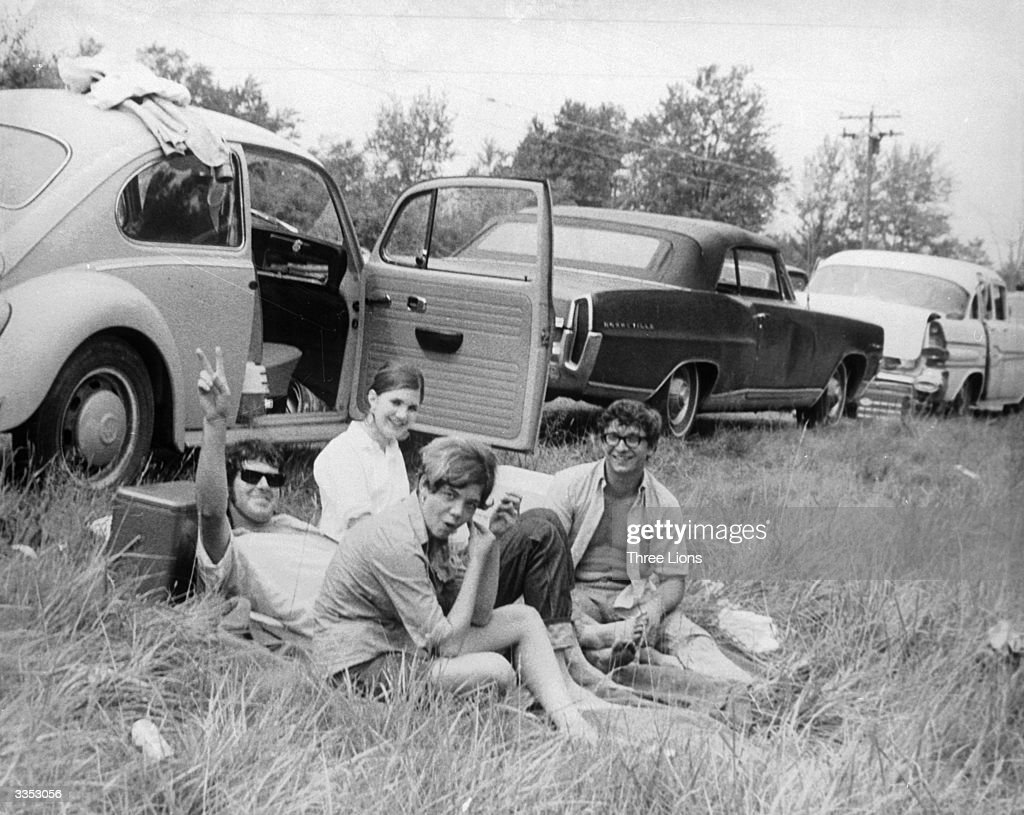 A group of friends sitting by their car at the Woodstock Music and Arts Fair one of them is giving a peace sign