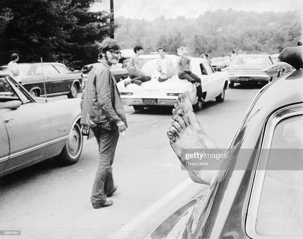 A man walking past a car notices the feet sticking out of the window during the Woodstock Music And Arts Fair.