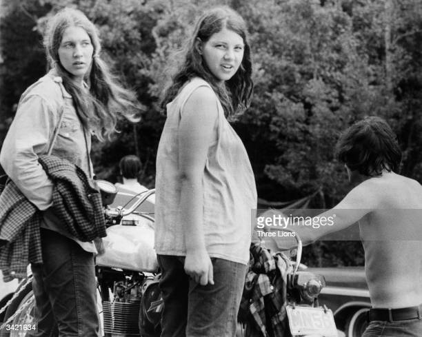 A pregnant woman and her friend wait as a motorcycle is unhitched from a car as they prepare to leave Max Yasgur's Bethil farm and the Woodstock...