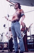 Fulllength portrait of English singer Joe Cocker wearing a tiedyed shirt and blue jeans performing at the Woodstock Music Festival in Bethel New York