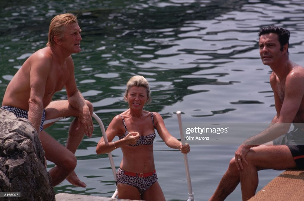 Kirk Douglas Louis Jourdan and Jourdan's wife Quiquie enjoying the water at the Eden Roc annex to the Hotel du Cap d'Antibes on the French Riviera