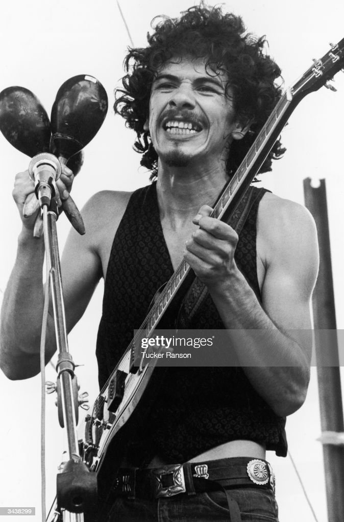 Mexican-born American guitarist and bandleader <a gi-track='captionPersonalityLinkClicked' href=/galleries/search?phrase=Carlos+Santana+-+Musician&family=editorial&specificpeople=11497837 ng-click='$event.stopPropagation()'>Carlos Santana</a> holds maracas and an electric guitar while performing at the Woodstock Music Festival in Bethel, New York.