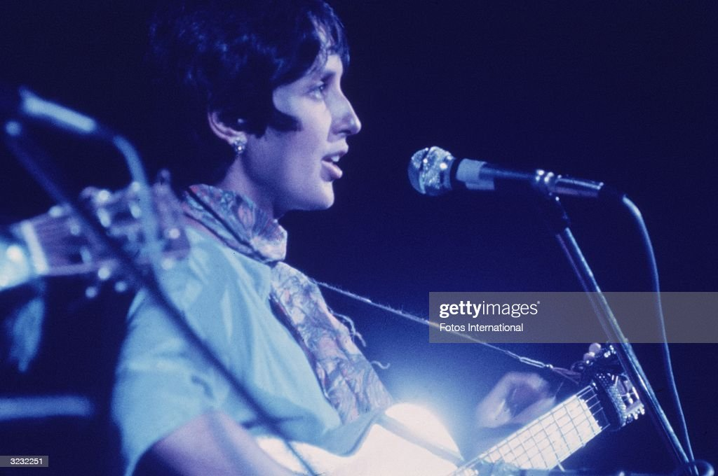 Profile of American folk musician Joan Baez singing and playing the guitar at the Woodstock Music Festival, Bethel, New York.