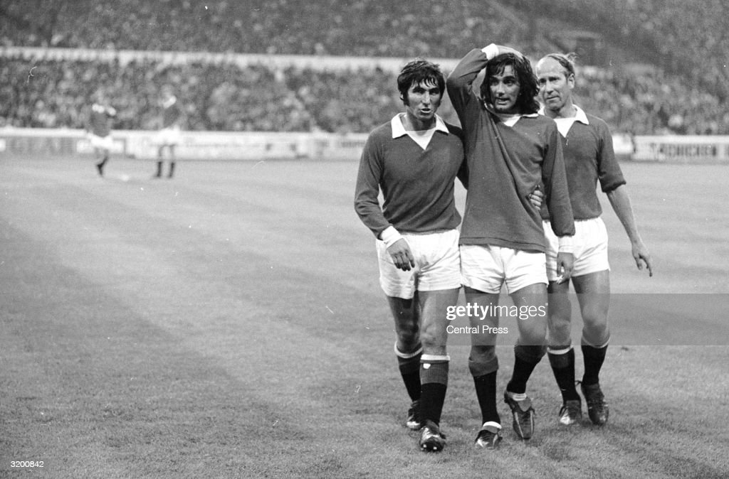 An unbelieving <a gi-track='captionPersonalityLinkClicked' href=/galleries/search?phrase=George+Best&family=editorial&specificpeople=206235 ng-click='$event.stopPropagation()'>George Best</a>, the Manchester United and Irish International, is helped off the field by teammates (on the right) Bobby Charlton and (on the left) Tony Dunne during a match against Chelsea at Stamford Bridge.