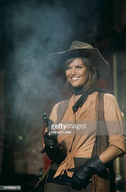 August 1971 filming a scene from the movie 'Petroleuses' ChristianJaque Claudia Cardinale in costume of the Far West holding a gun