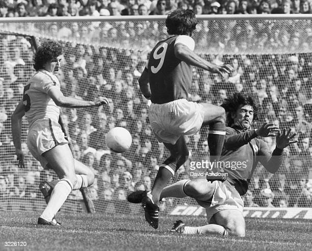 Leeds players Paul Hart and goalkeeper Harvey attempt to block an attack on the Leeds goal by Arsenal's Malcolm MacDonald
