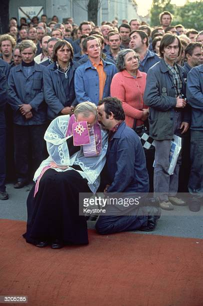 A member of the Trade Union Solidarity who are on strike at the Lenin Shipyard in Gdansk receives a blessing from a priest of the Catholic Church The...