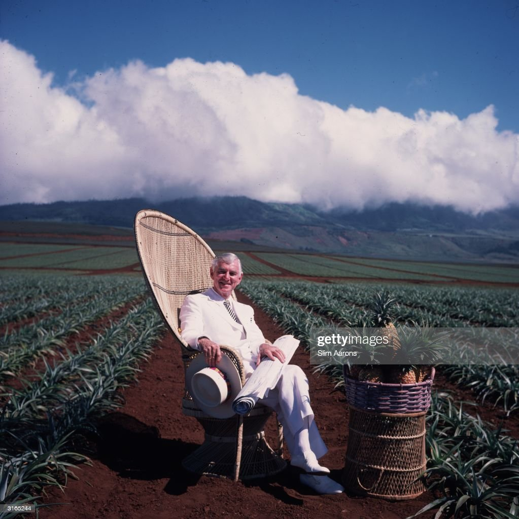 American entrepreneur David Murdock relaxes on a wicker chair on his plantation in Lanai, Hawaii. A basket of pineapples sits on a table in front of him.