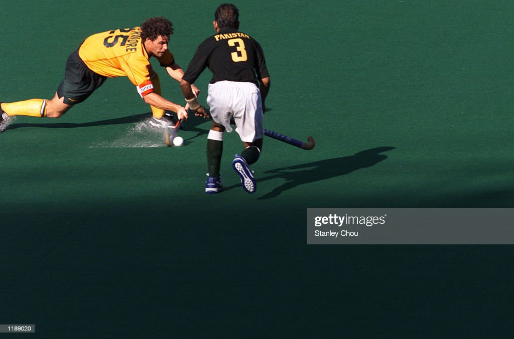 Brent Livermore of Australia slices the ball away from Muhammad Khalid of Pakistan at a third placing playoff match during the Sultan Azlan Shah Cup...