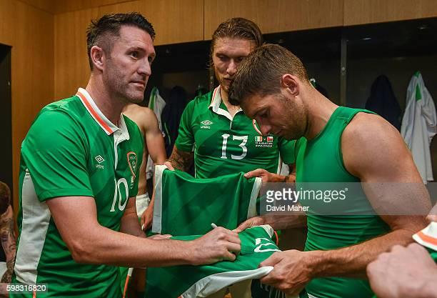 31 August 2016 Robbie Keane of Republic of Ireland signs jerseys for Wes Hoolahan right and Jeff Hendrick in the dressing room following the Three...