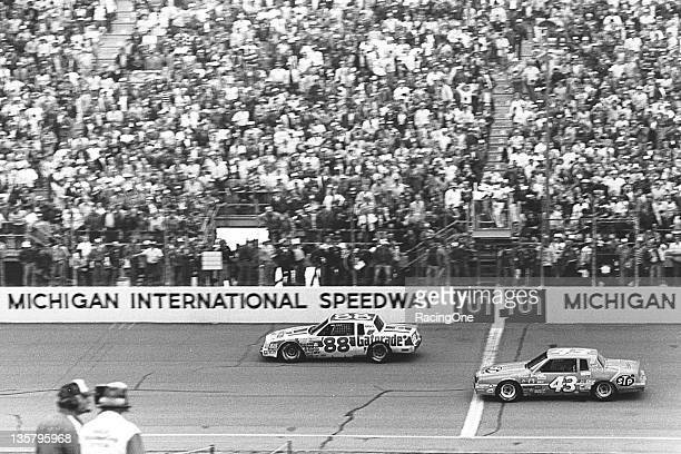 Bobby Allison takes the checkered flag just ahead of Richard Petty to win the Champion Spark Plug 400 NASCAR Cup race at Michigan International...