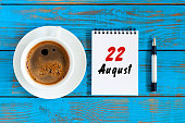 August 22nd. Day 22 of month, daily calendar on blue background with morning coffee cup. Summer time. Unique top view.