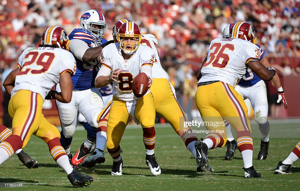 Washington Redskins quarterback Rex Grossman (8) fakes the hand-off to running back Roy Helu (29) during action against the Buffalo Bills on August 24, 2013 in Landover, MD