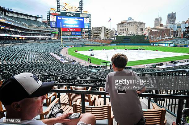 This young Detroit area baseball fan wears his New York Yankees shortstop Derek Jeter jersey as his dad a Detroit Tigers fan sits and waits out a...
