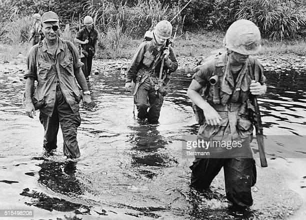 August 7 1966Da Nang South Vietnam General Moshe Dayan former chief of staff of the Israeli Army fords a stream with a US Marine reconnaissance...