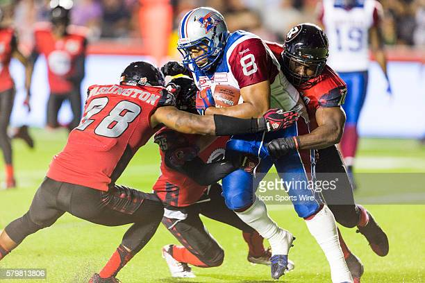 Montreal Alouettes Nik Lewis is tackled by Ottawa RedBlacks Jacques Washington Brandyn Thompson and Malik Jackson during Canadian Football League...