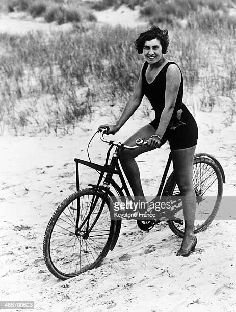 Tennis player Senorita Alvarez wearing a swimming costume on her bicycle in August 1929