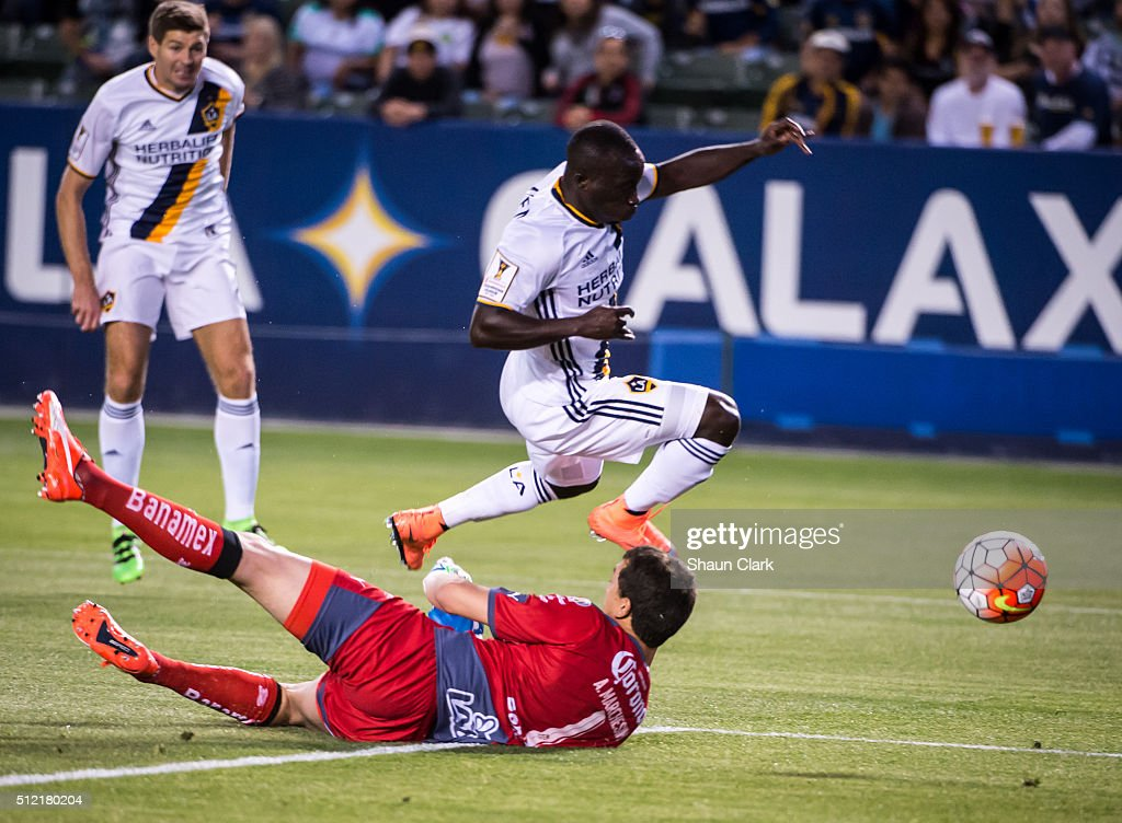 Augustin Marchesin of Santos Laguna makes a save as Emmanuel Boateng of Los Angeles Galaxy charges in on goal during the CONCACAF Champions League...