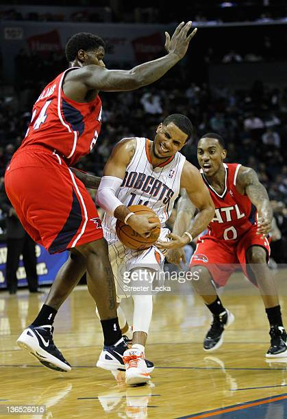 J Augustin of the Charlotte Bobcats dribbles through teammates Marvin Williams and Jeff Teague of the Atlanta Hawks during their game at Time Warner...