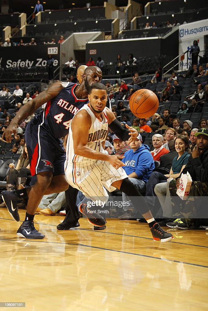 D.J. Augustin #14 of the Charlotte Bobcats grabs a pass against Ivan Johnson #44 of the Atlanta Hawks on December 19, 2011 during the preseason game at the Time Warner Cable Arena in Charlotte, North Carolina.