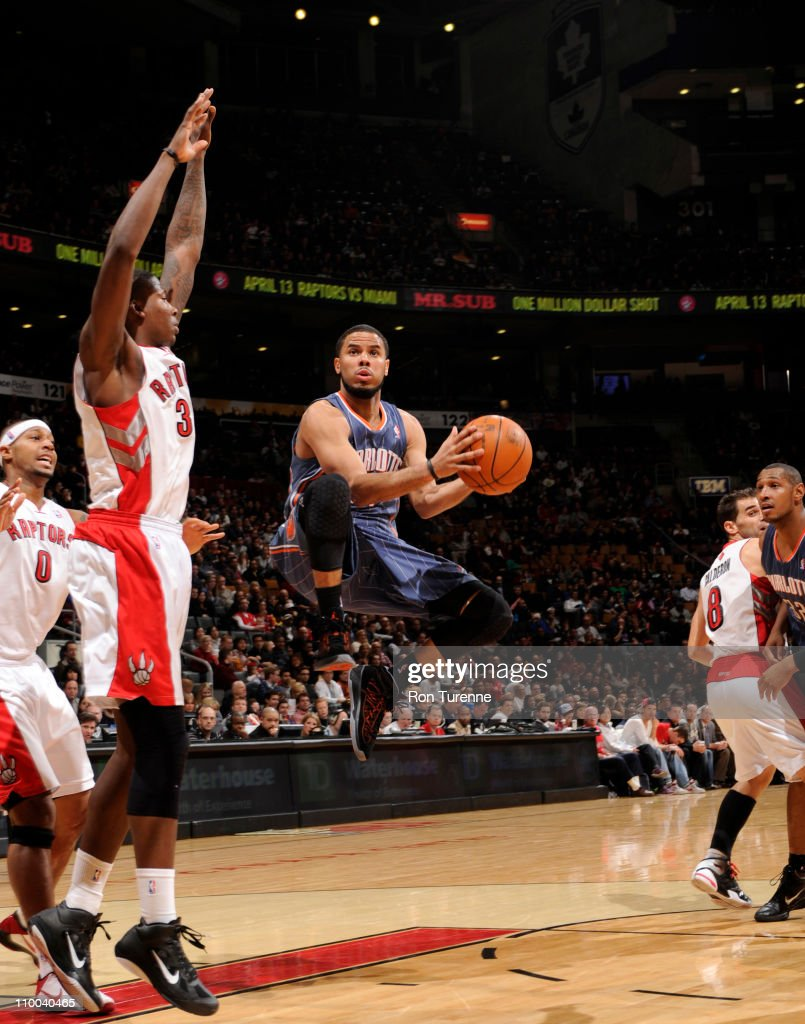 J Augustin of the Charlotte Bobcats shoots against Ed Davis of the Toronto Raptors during the game on March 13 2011 at the Air Canada Centre in...