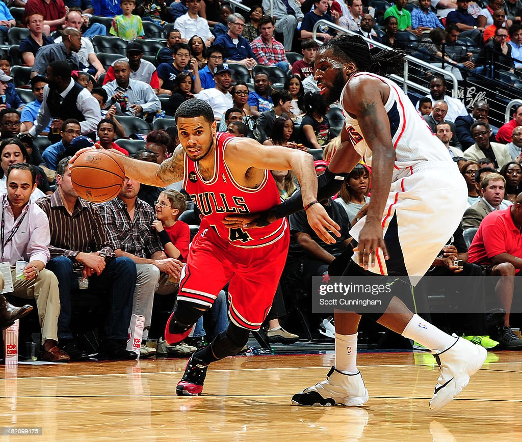 D.J. Augustin #14 of the Chicago Bulls drives against DeMarre Carroll #5 of the Atlanta Hawks on April 2, 2014 at Philips Arena in Atlanta, Georgia.
