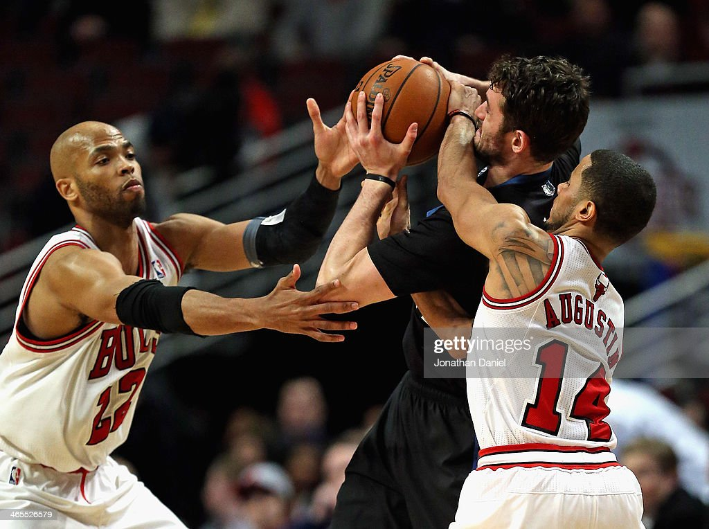D.J. Augustin #14 of the Chicago Bulls fouls Kevin Love #42 of the Minnesota Timberwolves as Taj Gibson #22 reaches for the ball at the United Center on January 27, 2014 in Chicago, Illinois. The Timberwolves defeated the Bulls 95-86.