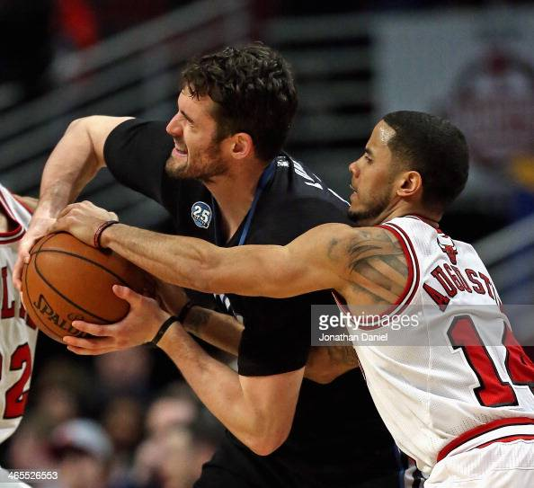 J Augustin of the Chicago Bulls fouls Kevin Love of the Minnesota Timberwolves at the United Center on January 27 2014 in Chicago Illinois The...