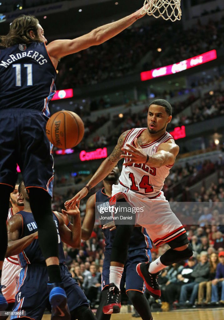 <a gi-track='captionPersonalityLinkClicked' href=/galleries/search?phrase=D.J.+Augustin&family=editorial&specificpeople=3847521 ng-click='$event.stopPropagation()'>D.J. Augustin</a> #14 of the Chicago Bulls passes around <a gi-track='captionPersonalityLinkClicked' href=/galleries/search?phrase=Josh+McRoberts&family=editorial&specificpeople=732530 ng-click='$event.stopPropagation()'>Josh McRoberts</a> #11 of the Charlotte Bobcats at the United Center on January 11, 2014 in Chicago, Illinois. The Bulls defeated the Bobcats 103-97.