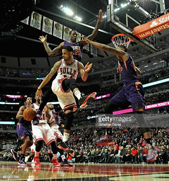 J Augustin of the Chicago Bulls passes the ball behind to Jimmy Butler as Archie Goodwin and Marcus Morris of the Phoenix Suns defend at the United...
