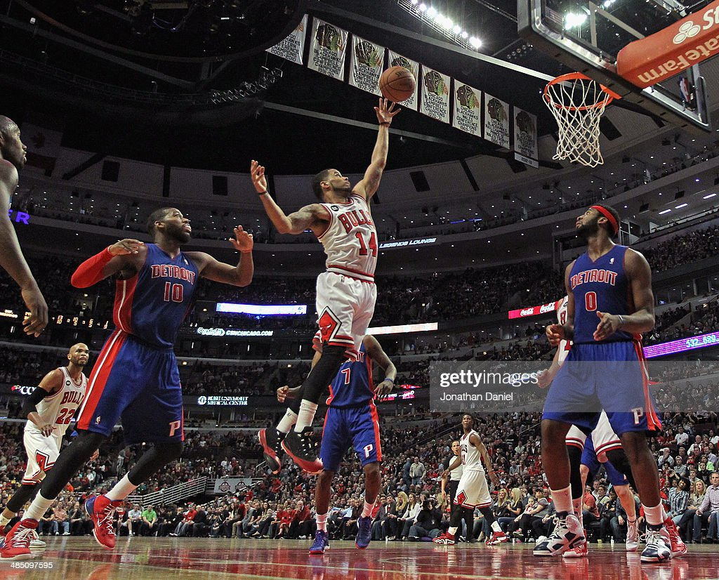 D.J. Augustin #14 of the Chicago Bulls shoots between Greg Monroe #10 (L) and Andre Drummond #0 of the Detroit Pistons at the United Center on April 11, 2014 in Chicago, Illinois. The Bulls defeated the Pistons 106-98.