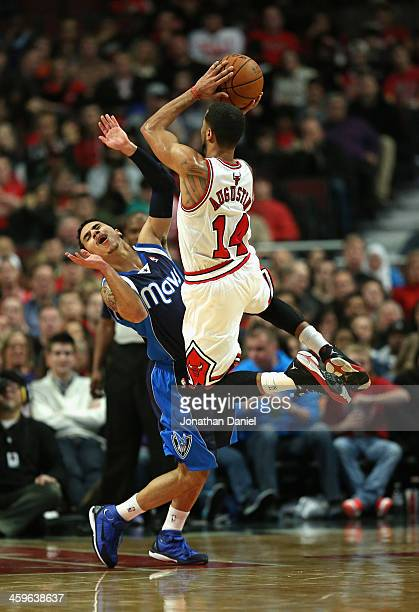 J Augustin of the Chicago Bulls shoots over Shane Larkin of the Dallas Mavericks at the United Center on December 28 2013 in Chicago Illinois NOTE TO...