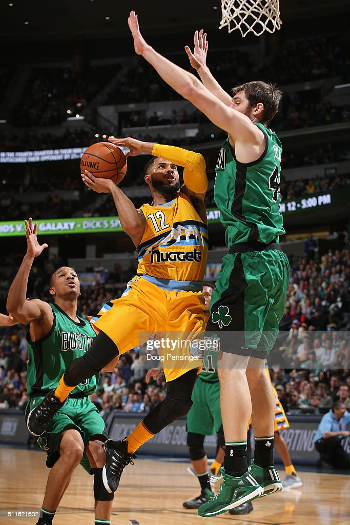J Augustin of the Denver Nuggets tries to get off a shot against Tyler Zeller of the Boston Celtics at Pepsi Center on February 21 2016 in Denver...
