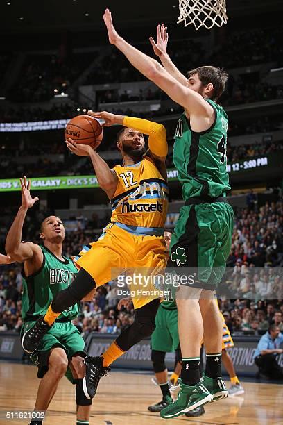 J Augustin of the Denver Nuggets tries to get off a shot against Tyler Zeller of the Boston Celtics at Pepsi Center on February 21 2016 in Denver...