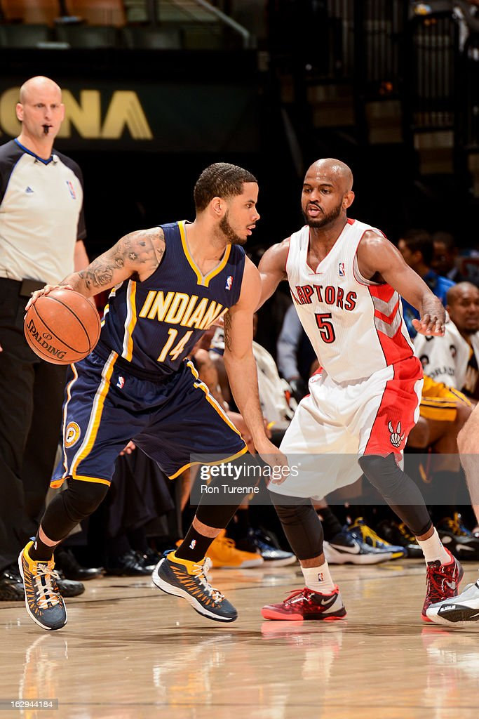 D.J. Augustin #14 of the Indiana Pacers controls the ball against John Lucas #5 of the Toronto Raptors on March 1, 2013 at the Air Canada Centre in Toronto, Ontario, Canada.