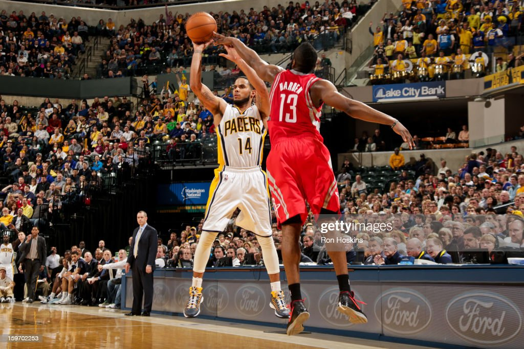 D.J. Augustin #14 of the Indiana Pacers shoots a three-pointer against James Harden #13 of the Houston Rockets on January 18, 2013 at Bankers Life Fieldhouse in Indianapolis, Indiana.