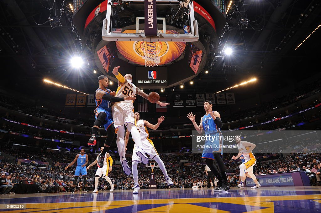 J Augustin of the Oklahoma City Thunder passes the ball to Enes Kanter against Robert Sacre of the Los Angeles Lakers on March 1 2015 at Staples...