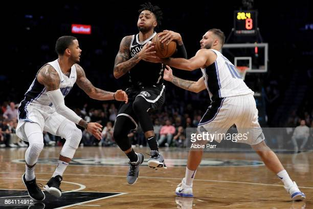 J Augustin of the Orlando Magic and Evan Fournier of the Orlando Magic defend against D'Angelo Russell of the Brooklyn Nets in the second half during...